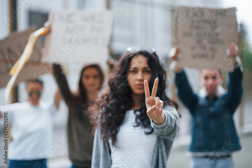 Fototapeta Showing gesture by two fingers. Group of feminist women have protest for their rights outdoors obraz