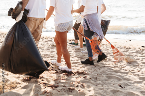 Photo of altruistic volunteers people cleaning beach from plastic trash Canvas Print