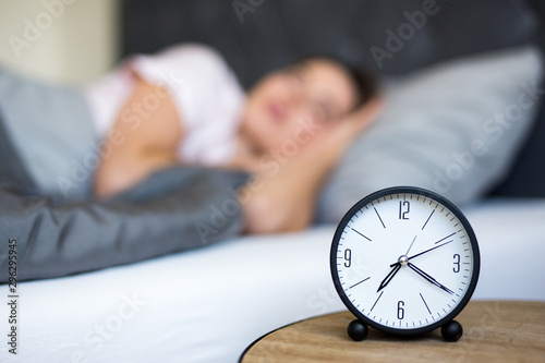 morning concept - young sleeping woman and alarm clock in bedroom Wallpaper Mural