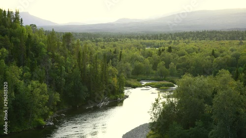 Wall mural - The sun setting over a river in a  green, mountain wilderness. Jamtland, Sweden.
