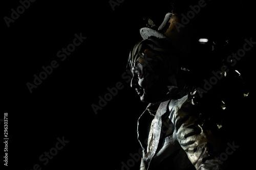 Fotografie, Obraz  Side view of mime imitating statue on black background