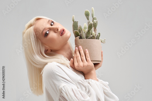 Fotografía  Beautiful blonde girl with make up holding pot with cactus