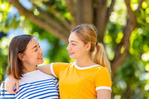 Photo Close up happy mother and daughter arm in arm outdoors