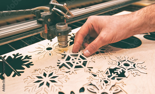 Fotografía  The man is working with laser cutter machine and takes  the finished product out