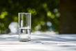 Leinwandbild Motiv fresh clean water in transparent glass at sunny day outside on wooden table