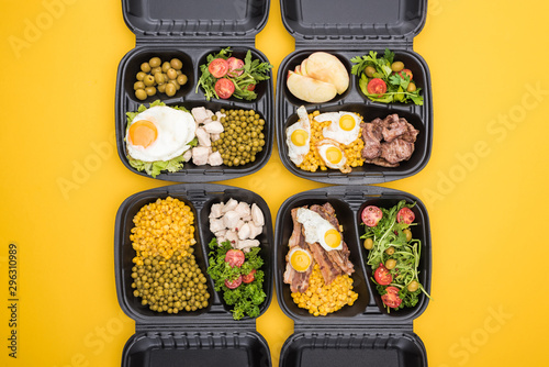 top view of eco packages with apples, vegetables, meat, fried eggs and salads isolated on yellow - 296310989