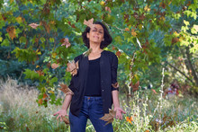 Latin Brunette Woman With A Black T-shirt In A Forest With Dry Leaves And Autumnal Colors, The Sun Enters Between The Branches Of The Trees.