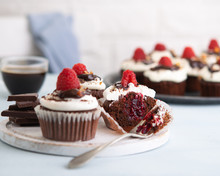 Raspberry Chocolate Cupcakes With Cupcake Cut In Half Jam Filling Cup Of Coffee And Fresh Raspberries On The Table, Light Background With Space Text. Recipe, Brunch, Party Concept.