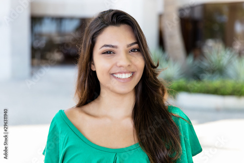 Photographie Portrait of laughing latin american young adult woman with long dark hair