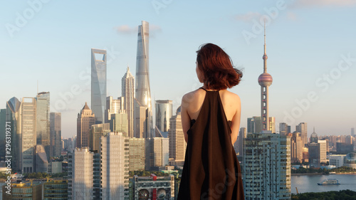 Montage in der Fensternische Shanghai Rear view of beautiful young brunette woman in sexy black dress posing on top of mansion roof with blur Shanghai Bund landmark buildings background. Emotions, people, beauty and lifestyle concept.