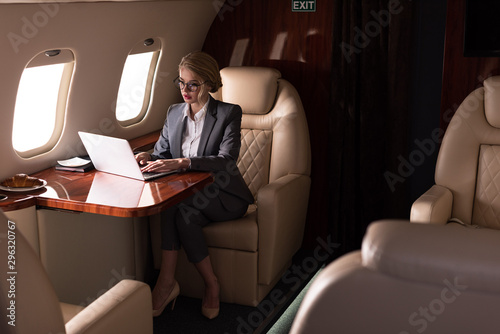 Fotomural  confident businesswoman working on laptop in plane during business trip