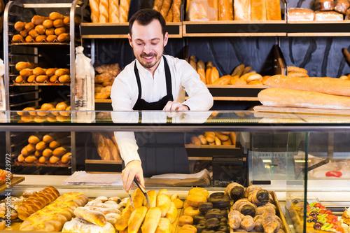 Foto op Plexiglas Bakkerij Salesman showing rolls and pastries