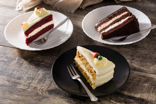 Assortment Of Sweet Cake Slices. Chocolate, Carrot And Velvet Cake Slices On Wooden Table