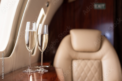 selective focus of interior of plane with champagne glasses for trip