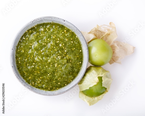 Tomatillo salsa verde. Bowl of spicy green sauce on white table, mexican cuisine. Top view.