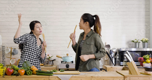 Two cheerful friends cook together and sing with spatulas as microphone. young japanese girls dancing and having fun in kitchen. ladies roommate making salad for healthy meal on weekend day time. - 296331773