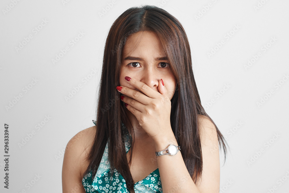 Fototapeta Shocked surprised thai asian young woman fearfully closes mouth with hand in summer dress isolated on white background, human emotions concept