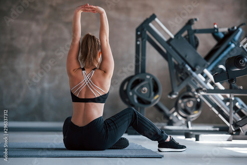 With hands up. Photo of gorgeous blonde woman in the gym at her weekend time
