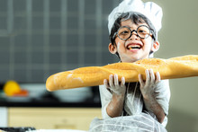 Lifestyle Family. Smiling Chef Asian Kid Boy Cooking Toast And Make  Bread For Dinner.  People Children Making And Leaning Sweet Food, So Happy And Enjoy.  Family Concept.