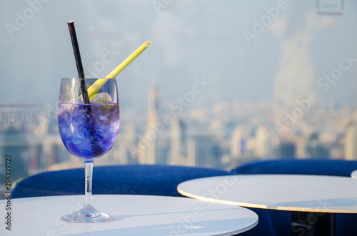 Iced cocktail glasses on the rooftop bar of Mahanakorn building in Bangkok with sunset background