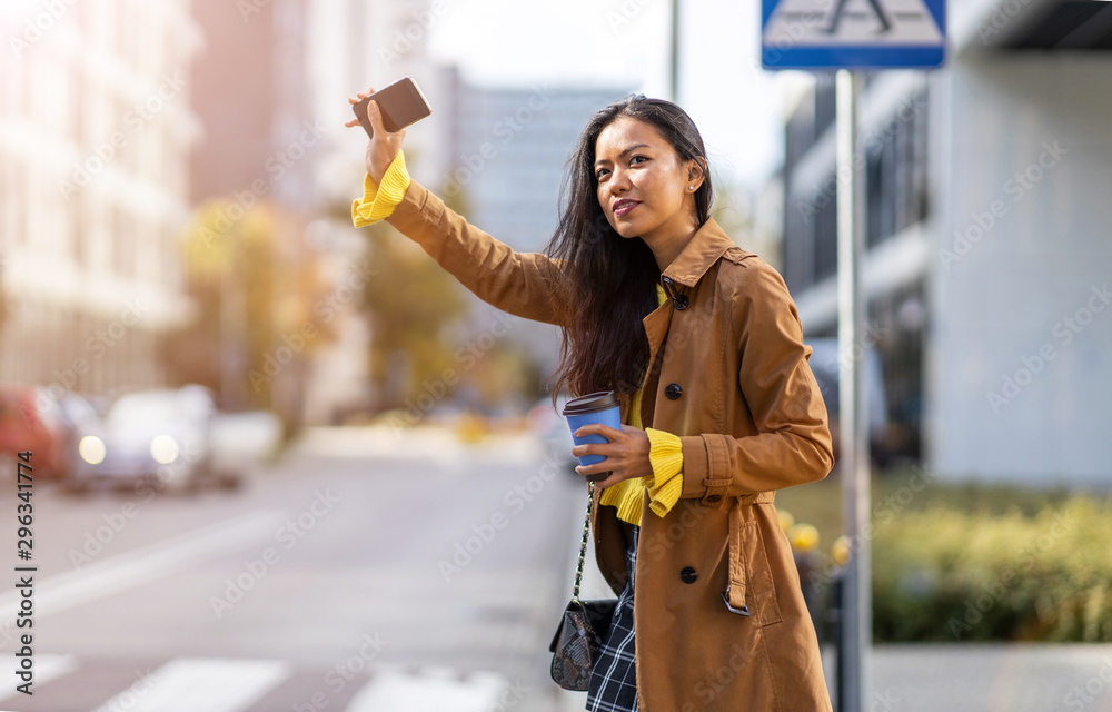 Fototapety, obrazy: Woman calling taxi on city street