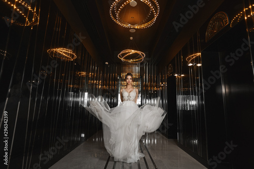 Beautiful leggy model girl in a wedding dress walking through the dark hall in a luxurious restaurant. Young woman bride in modish dress. Concept of wedding fashion.