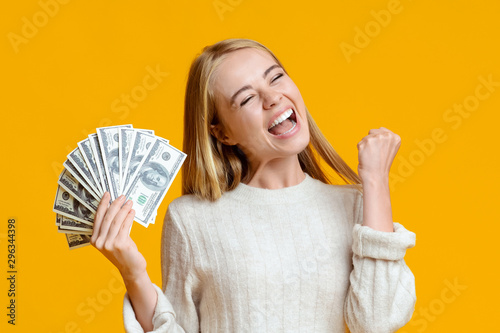 Fototapeta Millennial girl holding dollar bills and exclaiming with success. obraz