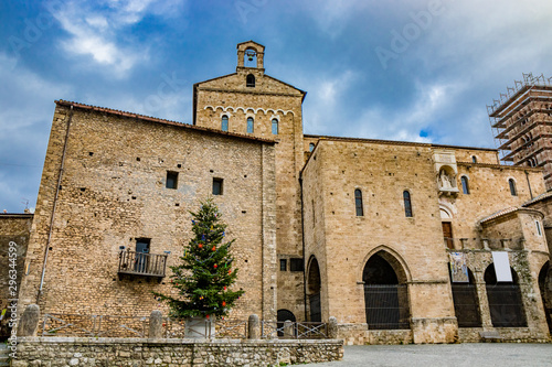 Fényképezés A large Christmas tree, decorated with colored balls, festoons and garland, red stars and lights, in the square of the medieval village of Anagni, near the cathedral