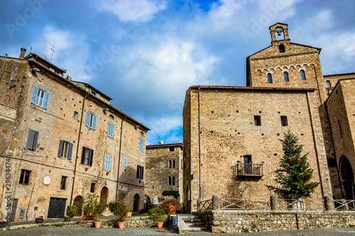 Photo A large Christmas tree, decorated with colored balls, festoons and garland, red stars and lights, in the square of the medieval village of Anagni, near the cathedral
