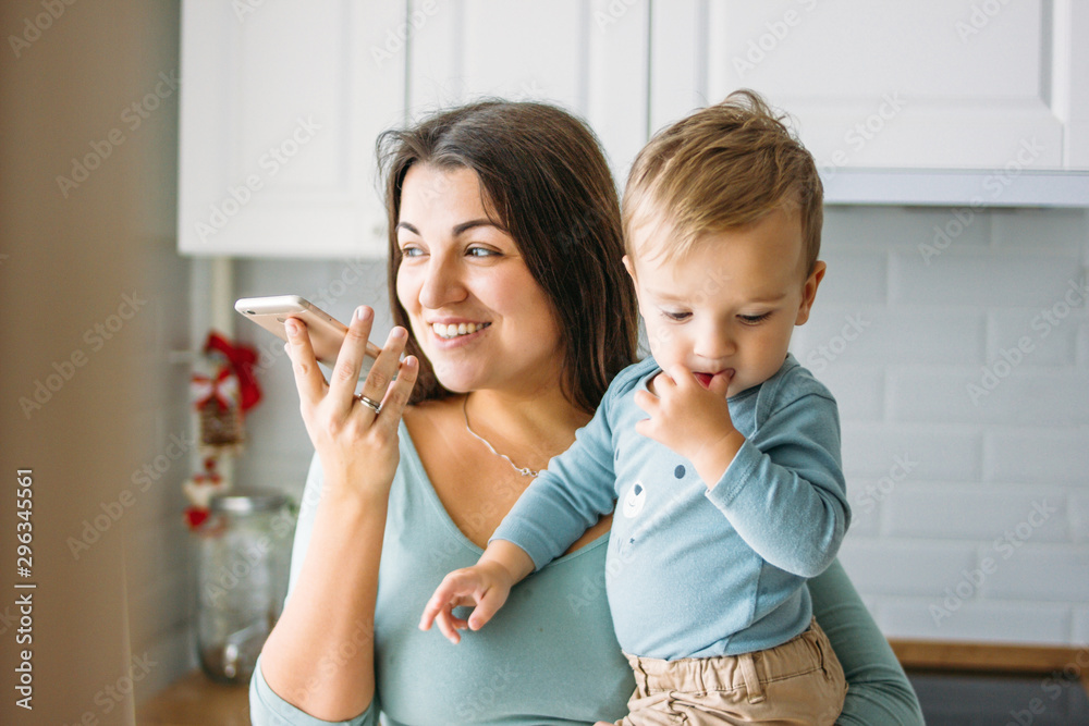 Fototapety, obrazy: The young carefree woman mom with baby boy in hands dictates voice message on mobile phone in bright kitchen