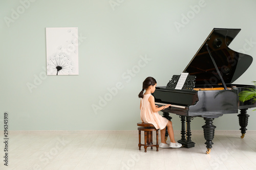 Little girl playing grand piano at home Wallpaper Mural