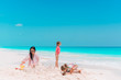 Family making sand castle at tropical white beach. Mother and two girls playing with sand on tropical beach