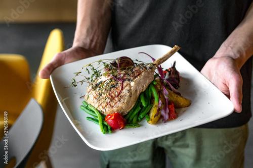 Fototapeta Kelner trzymający danie z mięsem i fasolką w restauracji obraz