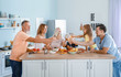 Big family clinking glasses during festive dinner at home