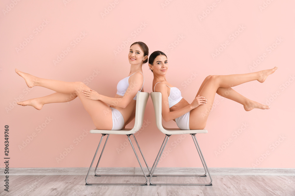Fototapeta Women with beautiful legs after depilation near color wall