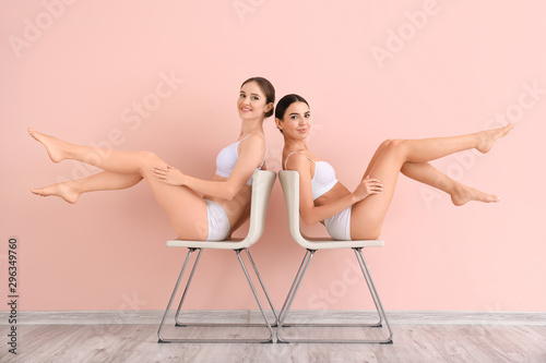 Obraz Women with beautiful legs after depilation near color wall - fototapety do salonu