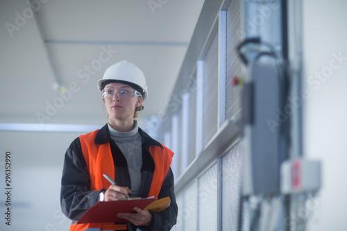 Photo Technikerin mit Helm überprüft Geräte