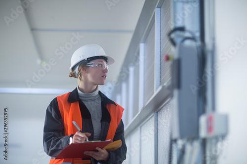 Cuadros en Lienzo  Technikerin mit Helm überprüft Geräte