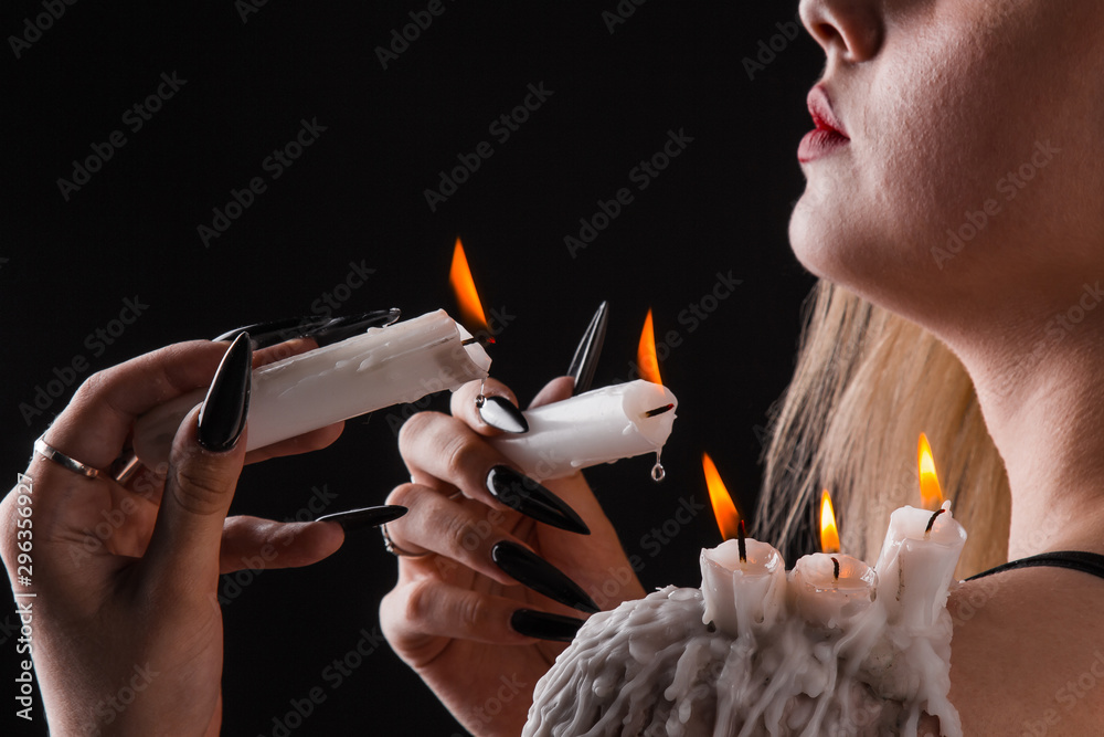 Fototapeta a girl with long hair in the image of a witch is trying to set herself on fire. rituals with candles for love spell and damage. expulsion of a bad spirit from the body.
