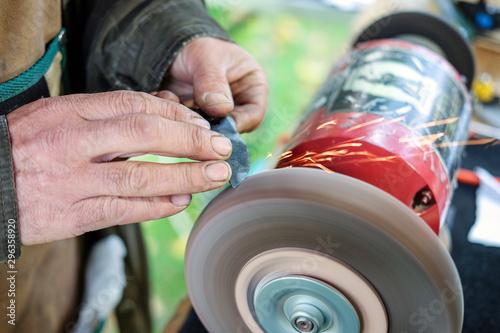 Fotografía Nahaufnahme: Handwerker beim Schärfen und Schleifen einer Klinge an einer Schle
