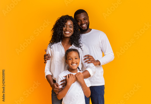 Happy Family Of Three Hugging And Posing Over Yellow Background Fototapet
