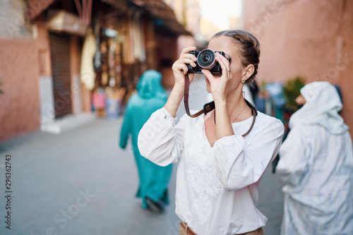 Obraz Tourism and technology. Happy young woman taking photo of  Marrakesh old town. Traveling by Morocco. - fototapety do salonu
