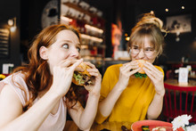 Two Female Friends Eating Burg...