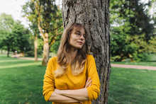 Young Woman At A Tree In Park ...