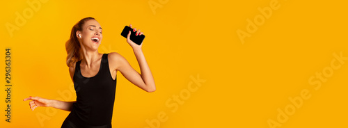 Woman In Wireless Earphones Holding Cellphone Dancing In Studio, Panorama