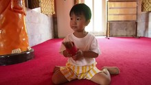 Asian Child Boy Holding And Shaking Red Wooden Bamboo Stricks Equipment Box Predict Fortune Teller In Buddhist Temple.