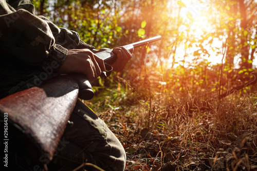 Fotografering A hunter with a gun in his hands in hunting clothes in the autumn forest close-up