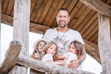 Happy Father With Three Triplet Sisters At A Treehouse