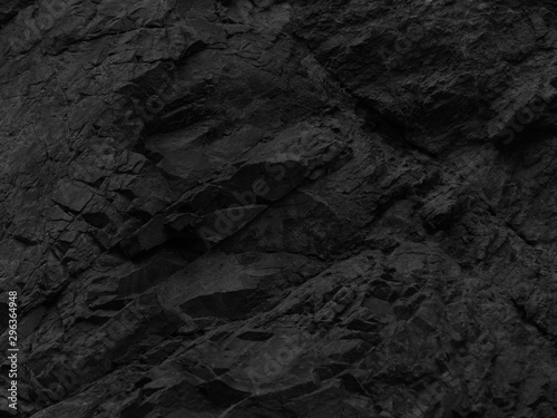 Black stone background. Mountain close-up. Fragment of the mountain. Black rock texture. - 296364948