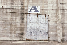 Close Up View Of Old Concrete Wall With A Chipping Wooden Door